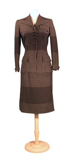 Irene Black and White Precision Suit   American, circa 1949. Woven in alternate rows of vertical stripes and windowpane checks, the jacket fitted through torso, wide notch collar, faux pocket flaps at left breast and each side front hip, self covered buttons down center front closure, set-in long sleeve with turn back cuff, black silk lining, skirt slit each side hem, two pleats each side front with vertical slit pocket. #vintage #1940s #fashion