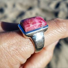 Take your breath away with this rare genuine Tugtupite sterling silver ring! Tugtupite has been used by Greenland Inuits for millennia. This crystal is extremely difficult to acquire because the ground in Greenland is frozen during most of the year and the Tugtupite mines are now closed. Tugtupite is made of a rare beryllium aluminum tectosilicate.  The cushion shaped thick Tugtupite cabochon glows a gorgeous salmon pink color under black UV light and intensifies to a magenta pink color when…