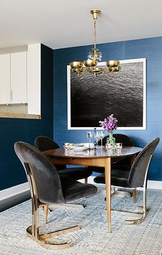 Gorgeous dining room with grasscloth walls, contemporary art and a bit of bling in velvet and brass chairs.