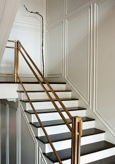 brass banister + black & white stairs