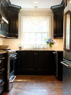 Black kitchen cabinets - love this idea only with the light cream walls and a natural colored tile