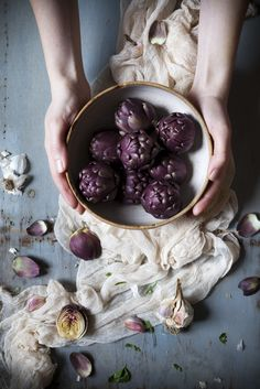 woman hands holding bowl full of raw purple artichokes on rustic wooden table with drape