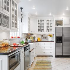 To-the-ceiling cabinets and trim, light-reflecting finishes, a built-in plate rack, a tiled toekick, and niches for the fridge, TV, and microwave add function and updated traditional style. | Photo: Ryan Kurtz