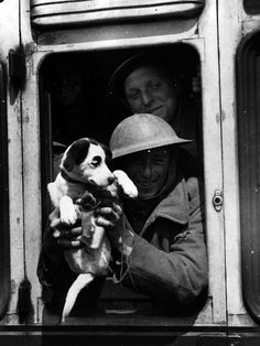 A member of the British Expeditionary Force smiles from the train window with his mascot having been safely evacuated back home from France.