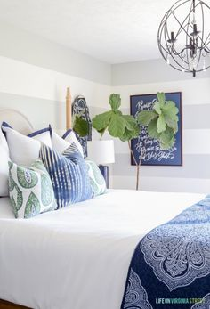 Updates: Summer Guest Bedroom Decor Bedroom with gray and white striped walls, white bedding, blue and green paisley pillows, navy blue linen lamps, iron orb chandelier and a navy blue Lindsay Letters Doxology canvas. Guest Bedrooms, Colorful Bedroom Design, Bedroom Green, White Guest Bedroom, Home Decor, Blue Bedroom, Guest Bedroom Decor, Striped Walls, White Bedding