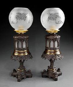 """A Pair of American Gothic Brass and Patinated Metal Oil Lamps On Stands Attributed To Dietz & Co., New York, Each Glass Font In Architectural Surround Of Gothic Tracery Windows, Burner Marked """"M.L. Collins"""", Stand With Molded Rim On Columnar Standard, Quatrefoil Base With Putto Marks, Etched Glass Shade   c. 19th Century"""