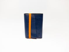 Product description:Blue full-grain vegetable tanned goat leather wallet. Single pattern folded and hand stitched with orange waxed linen thread. Orange flat braided elastic.5 individual compartments: 4 pockets that can hold up to 10 cards plus one slot where most international currencies fit without previous folding.Dimensions filled with 10 cards: 92x65x15mm /3.6x2.56x0.59 in (approx.)