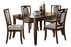 "The Martini Studio Extension Dining Table from Ashley Furniture HomeStore (AFHS.com). The dark brown burnished finish of the ""Martini Studio"" dining collection features rich birch veneers along with nickel color hardware and slate color upholstered chair seat and backs to create an inviting contemporary design that enhances the beauty of any dining experience."