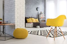 Spacious bedroom with white brick wall. Wooden coffee table and yellows chairs. By the wall grey bed with yellow pillows Grey Headboard, Grey Bedding, White Brick Walls, Grey Walls, Brick Wall Bedroom, Style Français, Contemporary Bedroom Furniture, Brown House, Lounge Chair Design