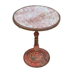 A handsome original  example of a round Bistro or Café Table from Paris, France, circa 1900-1930 With old red marble top, decorative brass edging and