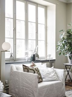 White interior from Entrance Realtors | large windows | white linen armchair | brass flos lamp | Scandinavian style decor | Nail the trend with an IKEA Karlstad armchair with a Loose Fit Urban Bemz cover