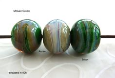"""Using Effetre Mosaic Green - """"didn't play nice with the silver glass on the plunged dot beads , but worked much better on the swirl style. I did two with Aurae the second time i decided to completely saturate the green , and it worked qiute well"""""""