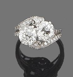 A diamond crossover ring, circa 1930 Obliquely-set with two old brilliant-cut diamonds, to single-cut diamond scrolling shoulders, principal diamonds approx. 2.50ct. total