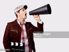 Young man wearing a flat hat, red plaid shirt and maroon jacket shouting on old fashioned megaphone while holding film slate.Megaphone is in his left hand.He is located on the left side of frame and...