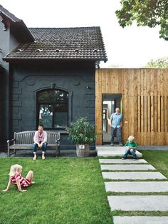 A family of cost-conscious Hamburgers converted a kitschy turn-of-the-century villa into a high-design home with a strict budget in place. To unite the quaint masonry of the original villa with the squat, ugly add-on built flush against it, the architects decided to paint the old-fashioned facade graphite gray and then covered the box next door in plain, light-colored larch. Photo by Mark Seelen.