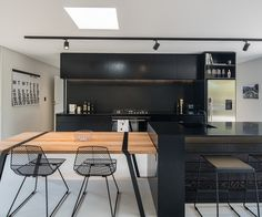 The black-and-white kitchen also features a movable table adjacent to the island. Photograph by Jeremy Toth.