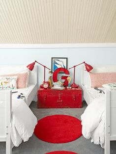 "The fire-engine red metal trunk is from a local junk shop. ""I wanted a low nightstand so my boys could reach everything,"" says Gretchen. The 20-inch-high trunk nestles nicely between the two beds."
