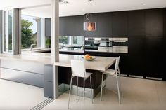 Black cabinetry with white bench tops