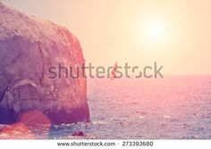 Man jumping from the rock into the sea - stock photo