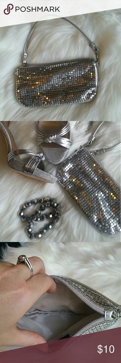 Silver Chain mail wristlet Perfect piece for a girls night out! 7.5 inch silver wristlet.  Fits most cell phones plus lipstick and other small essential for a night out. Zippered top. Slight pink staining on the inside lining on both sides. New York & Company Bags Clutches & Wristlets
