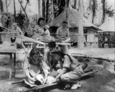 This October 1943 file photo shows U.S. Army nurse Nancy Cooke, left foreground, and Marie Carroll, right background, both of Philadelphia, Pa., helping bandage Chinese troops at a field hospital somewhere in the jungles of India during World War II. (AP Photo/Files)