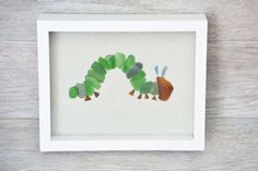 Very Hungry Caterpillar Wall Art, Sea Glass Art, Nursery Room Decor, Kids Room Wall Art by Seashore Secrets  This unique caterpillar was inspired while reading The Very Hungry Caterpillar to my son. Made from 100% genuine sea glass that was handpicked. Perfect piece to for your nursery or kids room!! The surf tumbled beach glass is kelley green and amber browns, with two rare pieces of blue for the antennas.  Set on a cream Muslin cloth backing.  The shadow box is 8x10 with a depth of 2. It…