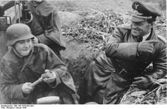A  Luftwaffe General smiling  and probably giving advices to a young soldier ( a boy soldier i say) while he's training with hand grenades. January 1945