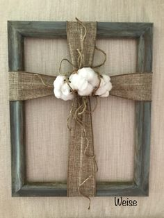 """Burlap cross and cotton bolls - repurposed 11"""" x 14"""" frame is painted with milk paint. Use 2.5"""" burlap to make a cross. Gather the center and tie with jute. Add strings of jute so the strings show on each branch of the cross.  Pick cotton before it is defoliated. Maintain cotton bolls with Calyx (dried flower part) in tact. Adhere cotton bolls to burlap by using hot glue on the Calyx. Created by:  Melanie Weise"""