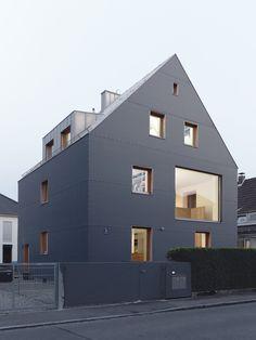 Der Materialmix aus dunkelgrauem Polyethylengewebe, Faserzement und Zinkblech sowie die in der Fassadenebene liegenden Fenster haben den 50e...