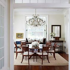 Prefer the dining room table and flowers be the focal point, rather than the rug.  Rug just needs to define the area.