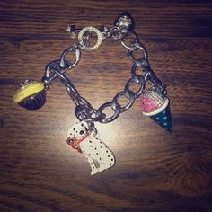 """Juicy Couture Charm Bracelet Authentic Juicy Couture charm bracelet in silver that comes with three separately purchased charms with room for many more! The snow cone and the Dalmatian charms are both 2013 limited edition and the cupcake charm is neat because the top pops open. The bracelet measures about 7"""" from one end to the other. Juicy Couture Jewelry Bracelets"""