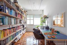Escritório tem prateleiras de madeira com livros organizados pela cor de suas lombadas.
