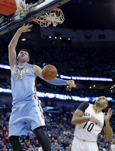 Description of . Denver Nuggets center Jusuf Nurkic (23) dunks next to New Orleans Pelicans guard Eric Gordon (10) during the first half of an NBA basketball game in New Orleans, Wednesday, Jan. 28, 2015. (AP Photo/Gerald Herbert)