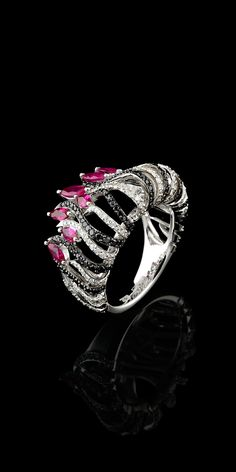 Kaleidoscope ring. Black & white diamonds and rubies in white gold.