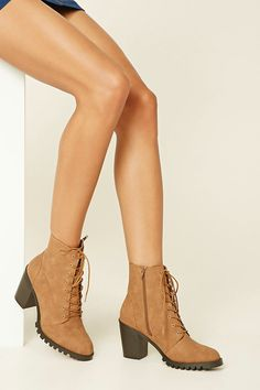 A pair of faux leather ankle booties featuring a lace-up front, almond toe, zipper side, block heel, and a ridged sole.