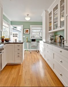 Kitchen paint color, green blue. Glass cabinets to countertop. Dark solid surface countertop.