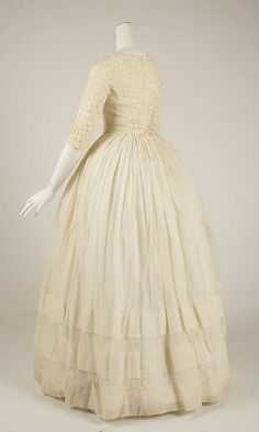 Afternoon dress, ca. 1843; cotton  Metropolitan Museum of Art C.I.45.68.28; Gift of Art Worker's Club, 1945  The extensive ruching on the bodice of this dress is similar to the more subdued gathering often used at the center front of both day and evening dresses of the period.  At the same time, the large tucks on the skirt and the light materials look forward to the lingerie dresses of the early twentieth century.