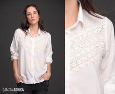 Camisa Adrika tiene un toque romántico especial. De corte clásico, manga larga y detalle de Giupiur diagonal en canesú, su paleta de colores es sobria y de vanguardia. ¡Mirala!