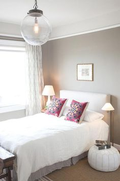 Chic bedroom features a clear glass globe pendant illuminating a white linen headboard on bed dressed with a white linen duvet, gray pleated bedskirt and pink pillows flanked by a Moroccan bedside table to the left and a white leather Moroccan pouf to the right illuminates by an antique brass floor lamp.