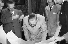 Alfred Agache (tirando os óculos da lapela) observa Manoel Ribas que analisa as plantas do Plano Diretor de Curitiba no Palácio São Francisco em 23 de outubro de 1943