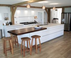 White bulthaup b1 kitchen with white AGA oven. Exposed beams and wooden bar stools complement the country aesthetic. #kitchens #b1 #aga #countryside #rustic