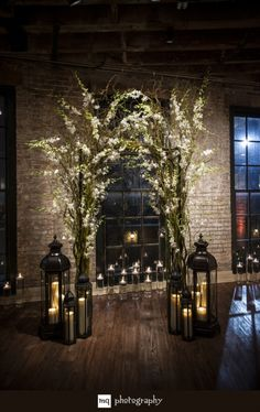 Pretty ceremony backdrop using lanterns, branches and flowers