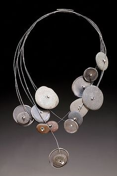 """TERRI LOGAN  The abstract jewelry forms of  Terri Logan's Colorado river rock creations are set in sterling  silver. Each rock has an energy of its own and personality which makes  for a dynamic grouping.  """"My work is based on formal concerns,  design and function. I make jewelry because of the intimacy the function  allows. I use metal and stones (river rocks) because they are  inherently strong materials."""