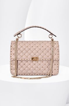 Signature studs emphasize the quilted texture of this covet-worthy bag by Valentino with a shiny chain shoulder strap and studded top handle to complete the modern, feminine design.