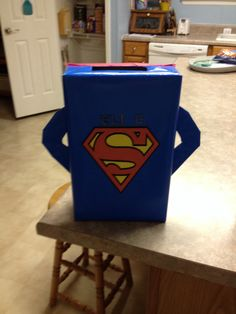 Superman Valentines Box- easy to make Wrap a cereal box with blue wrapping paper and cut out a center rectangle on the top; print out and tape/glue the superman logo on the center. To make the arms cut out from cardboard and wrap with blue paper then hot glue to sides. Finish by using a red plastic tablecloth piece for the cape. (Pic doesn't show, but it's glued to top of box behind opening)