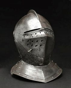 A close helmet probably German, mid-16th century - The one-piece skull with low, roped comb, top pierced with a single hole; back fitted with domed lining rivets, lower edge flanged  fitted with two-lame neck defense. Visor of prowed form having rectangular sights above a roped band  two rows of circular breaths, lower right section with two rows of keyhole breaths above the lifing peg. Bevor molded to the chin with central ridge  pivoting at the same point as the visor; upper rim beveled...