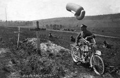 A motorcycle dispatch rider studying the details on a grave marker, whille in the background an observation balloon is preparing to ascend
