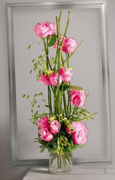 Bouquet linéaire vertical de roses roses gros boutons sur une structure de branchage vert et feuillage aérien. #rose #bouquet
