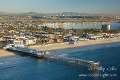 Crystal Pier, 872 feet long and built in 1925, extends out into the Pacific Ocean from the town of Pacific Beach. Mission Bay and downtown San Diego are seen in the distance. San Diego, California, USA. Obviously a current picture