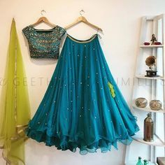 Beautiful blue color designer lehenga and blouse with parrot green color net dupatta. Blouse with hand embroidery work and lehenga with swirls at the bottom. 05 November 2017